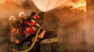 Die Feuerwehrmänner tragen zur Brandbekämpfung Atemschutz, der sie vor giftigen Rauchgasen schützt. Über Ihnen entwickelt sich eine Durchzündung von heißem Rauch, auch Flashover genannt.